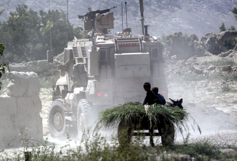Children aboard a farm cart watch as American armored vehicles pass through a dirt road near a pomegranate orchard in Arghandab Valley, southern Afghanistan