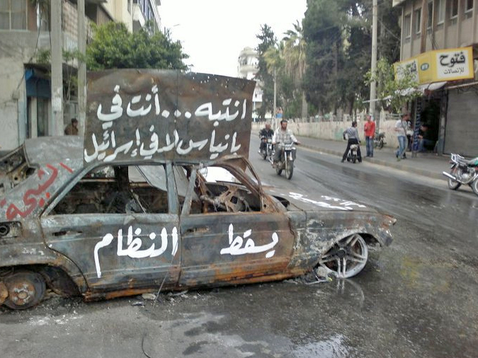 A burnt car in the coastal Syrian town of Banias
