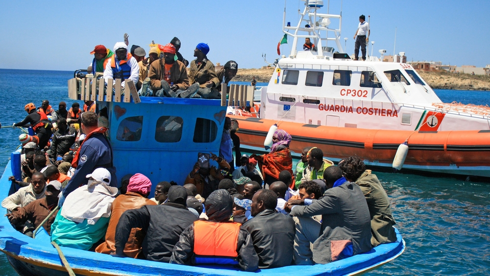 A boat carrying sub-Saharan African migrant workers arrives in Lampedusa from Tripoli. Thousands of migrants have made the perilous journey