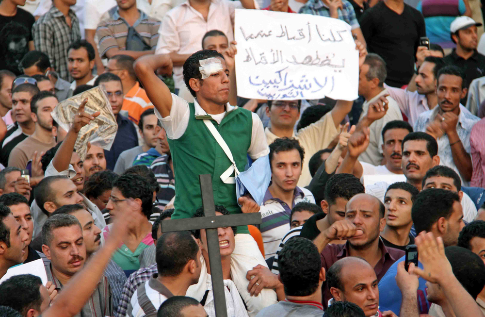 "A Muslim man holds a placard, reading: ""We are all Copts when Copts are persecuted"". Thousands of Christians and Muslims staged a protest in Cairo Monday against the reported excessive use of force by the nation's military against thousands of peace"