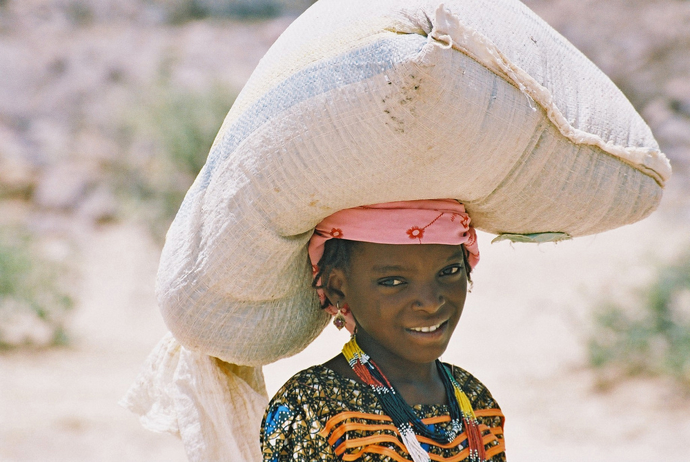 Girl carrying bag of food in Zinder region in Niger