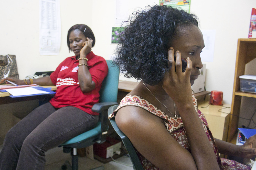 Nurses, Zainab Blell (r) and Mabel Kaitemoh, answer the constant stream of calls into the newly launched Fistula Hotline at the Aberdeen Women's Center, a clinic offering free fistula surgery in Freetown, Sierra Leone