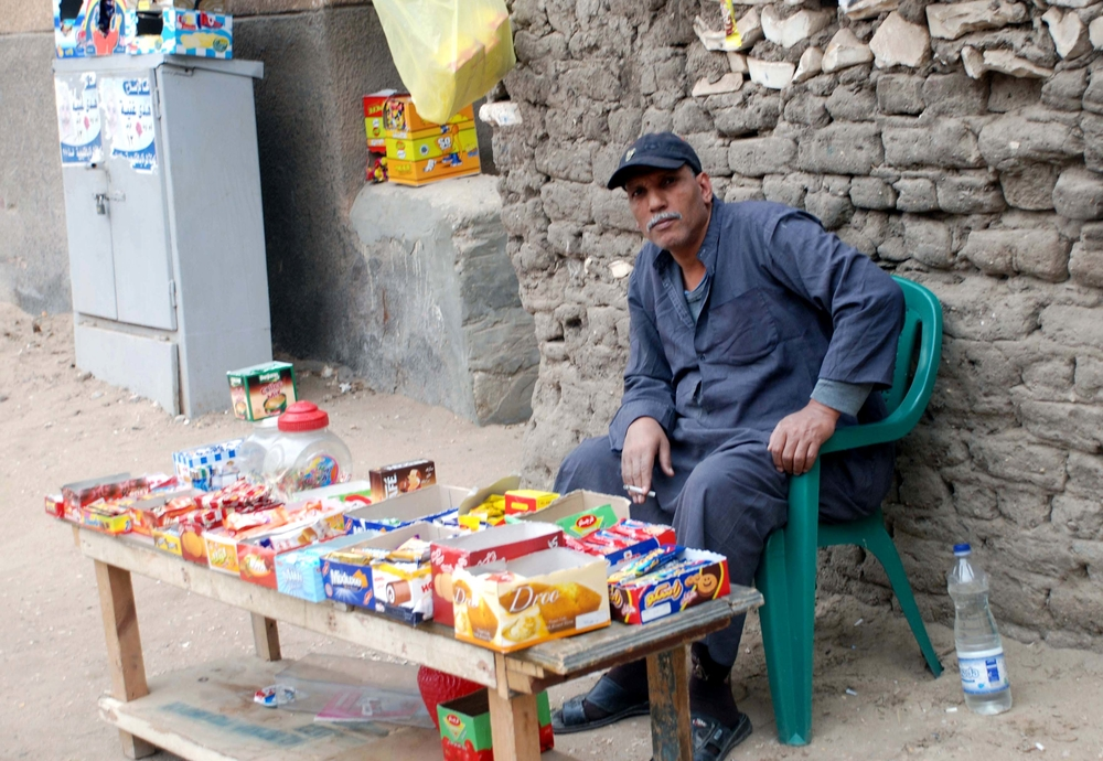 A poor Egyptian sells sweets on the street [which town/city] to earn a living
