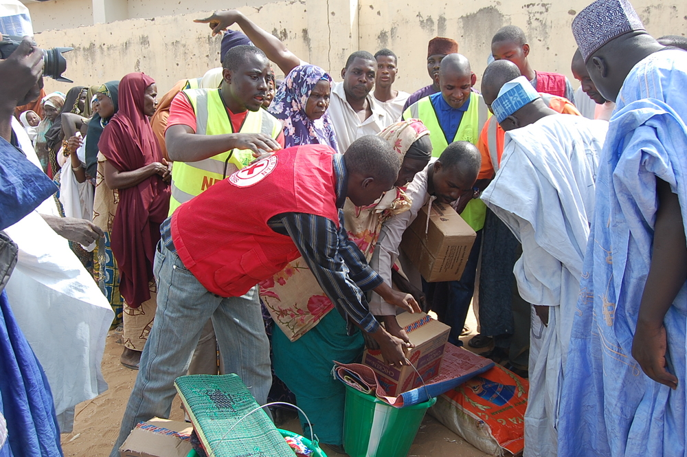 People displaced by Boko Haram attacks and the violence that ensued in Damaturu city, collect relief materials