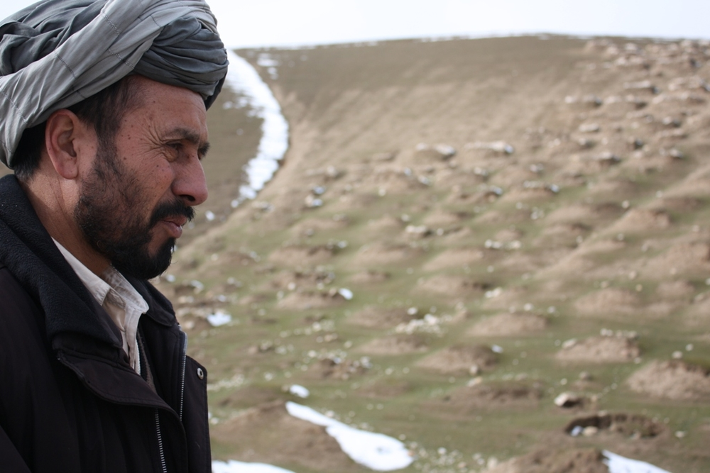 Mullah Najibullah, a member of the shura council in Pashtun Kot district in Faryab province, northern Afghanistan, stands before a cemetary. He says people in northern Afghanistan regularly die of hunger, cold and poverty, but have received less aid than