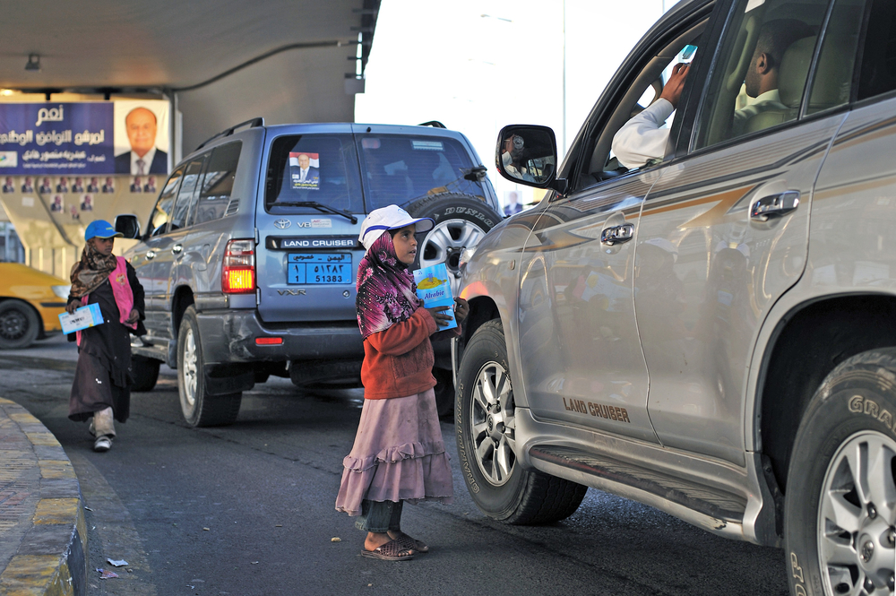 Yasmine Hajiri and her sister sell tissues to passing drivers at an intersection in downtown Sana'a on February 15, 2012. Hajiri's family took her and her sisters out of school so that they could help generate income by selling tissue after the family sto