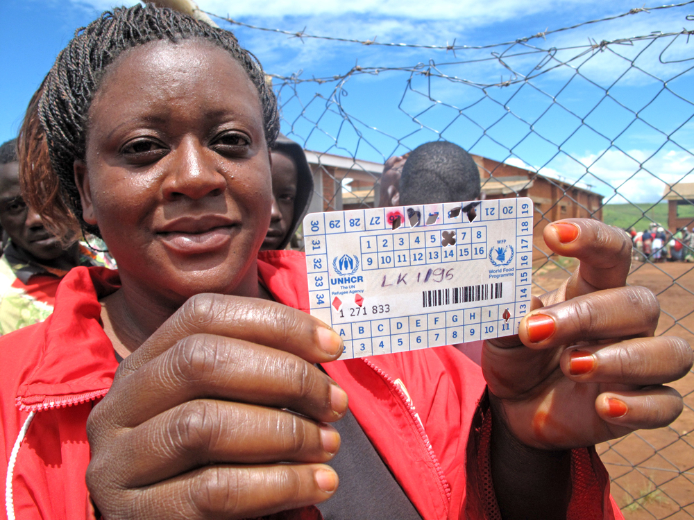 A refugee at Dzaleka camp in Malawi holds up her food ration card. The World Food Programme cut rations to refugees at Dzaleka by half in March 2012 due to a funding shortfall