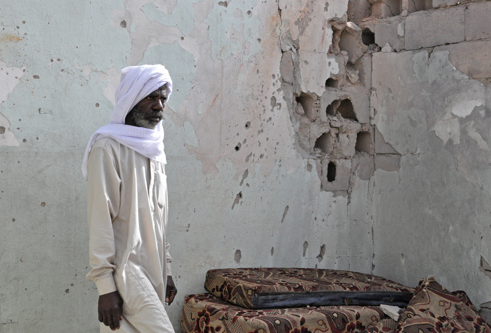 A resident of Tayuri stands against a bullet-riddled wall of his house. Part of it was destroyed during the clashes in Libya
