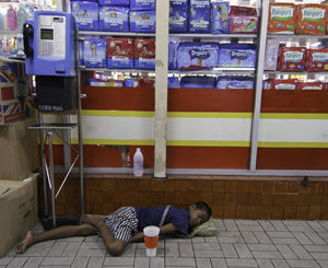 A young Cambodian beggar sleeps near a market on Patpong Steet  in downtown Bangkok. While begging is illegal it is tolerated in Bangkok as most of the beggars are not Thai