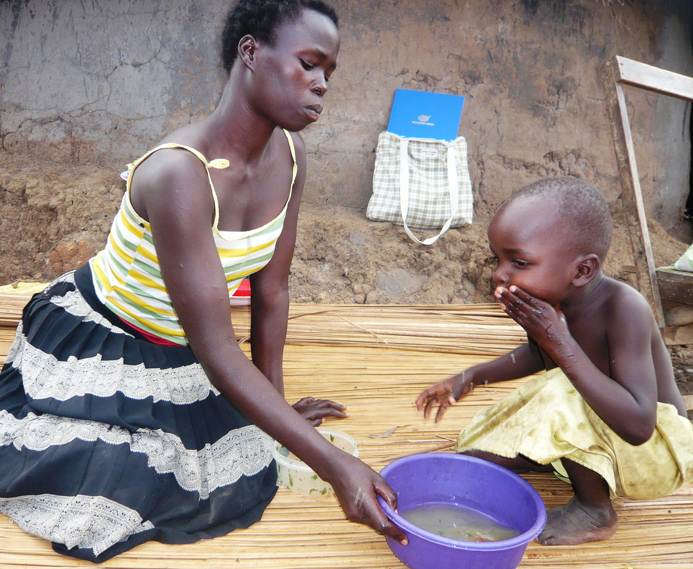 Jeniffer Abalo with her daughter washing hands after a meal in Gulu town
