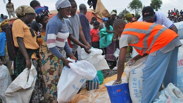 Aid workers fill bags of fortified cereal for new arrivals to the Mugunga camp in eastern DR Congo