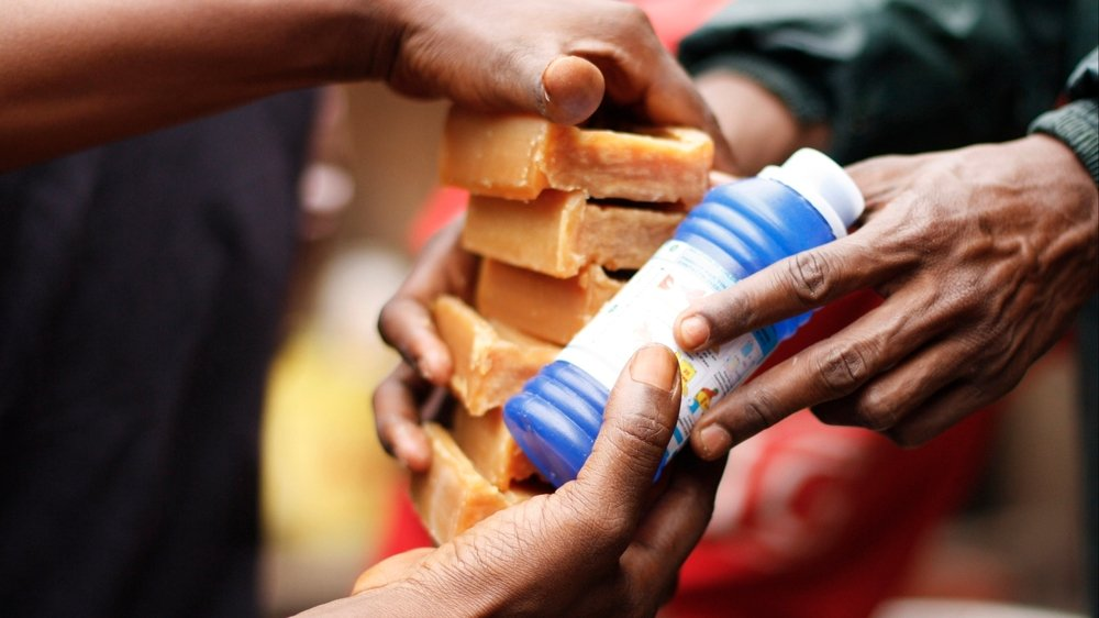 An aid worker distributes soap and bleach in Guinea's capital, Conakry, where people have been infected with cholera