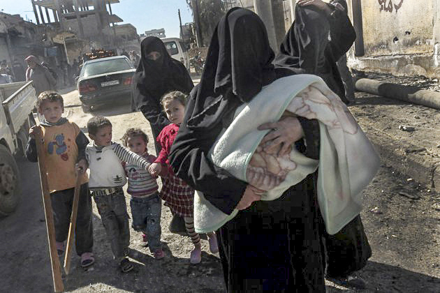 Syrian women and their children flee the violence in the northwestern city of Sermin