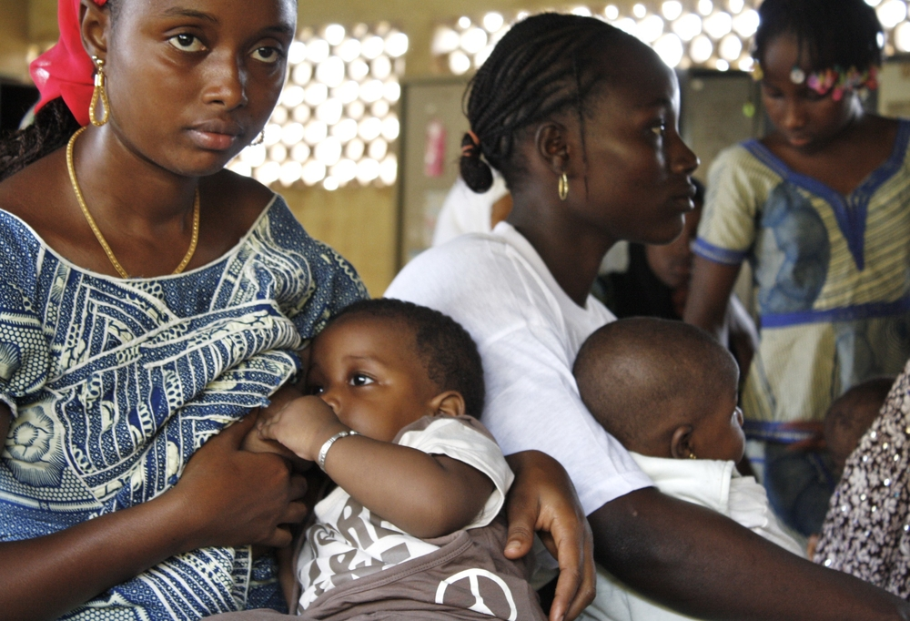 Women and their children at a community health centre in Guinea's capital Conakry. They come regularly to have their babies weighed and measured, to update vaccinations and to talk about proper child nutrition