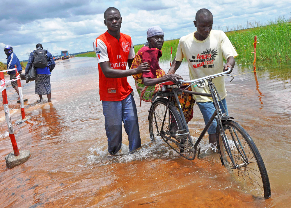 Soroti residents help an old woman to cross the flooded Awoja bridge in Teso sub region, Uganda (Sep 2012)