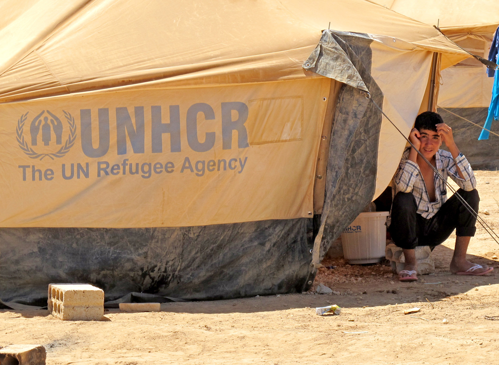 Syrian refugee boy sits in front of UNHCR provided tent in Zaatari Camp in Jordan