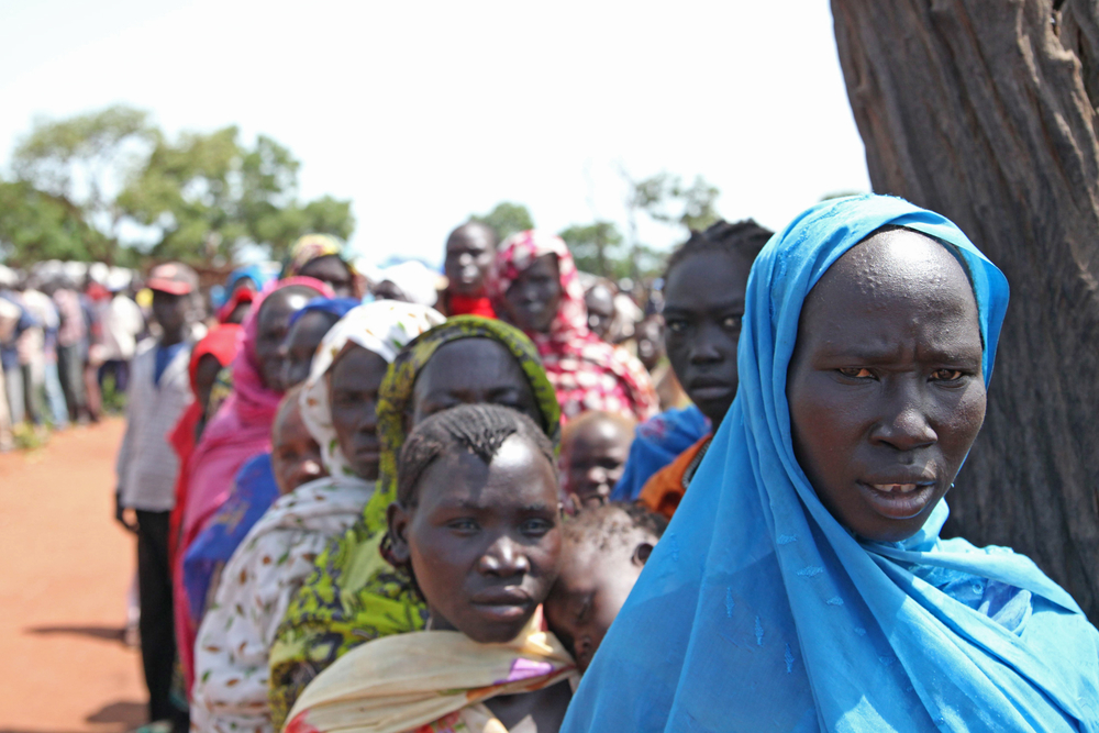 Women and men queue for salt and soap at Yida refugee camp in Unity State, South Sudan. Aid agencies are promoting hygiene measures, especially handwashing, to minimize diseases linked to poor sanitation