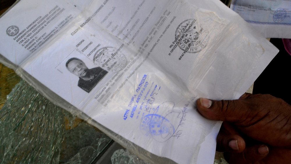 Francis William, a Tanzanian migrant living in Athens, shows his temporary asylum seeker document after his office was smashed up by a racist mob