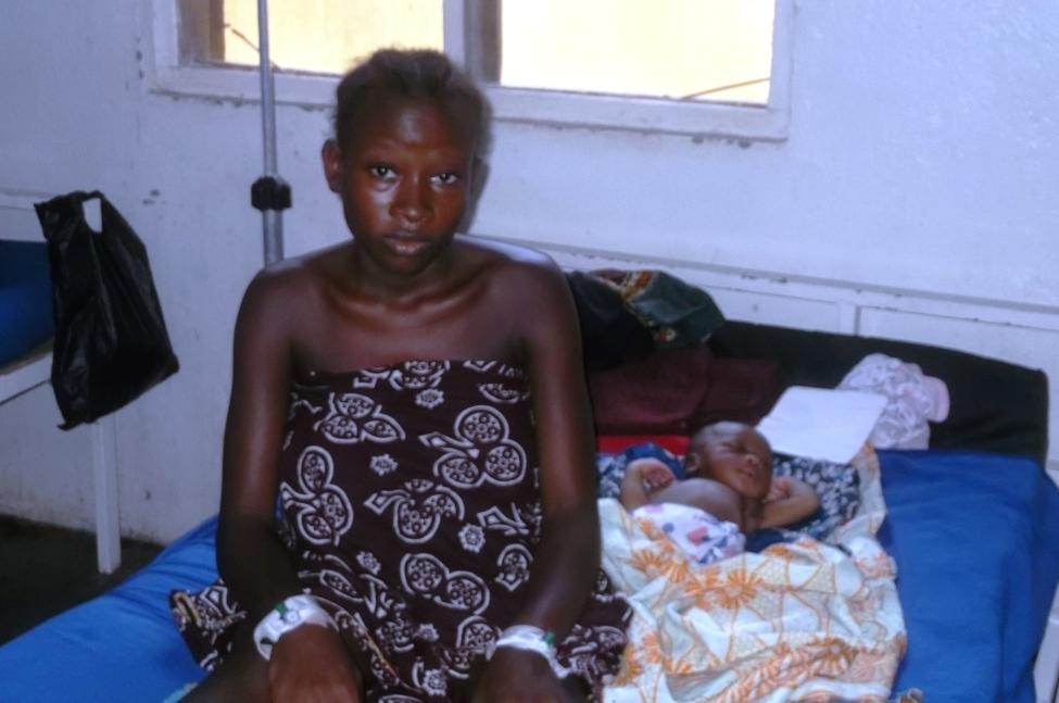 A young girl sits on a bed at the MSF Gondama referral hospital after she delivered her baby through caesarian operation