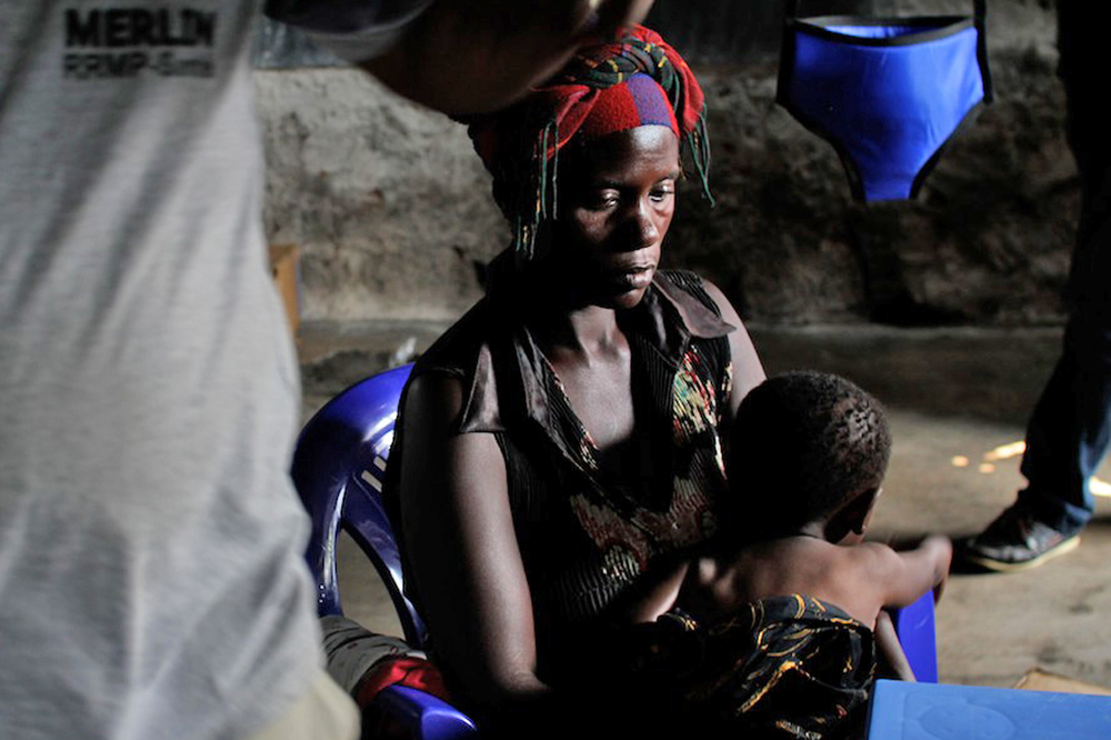 A woman with a malnourished child receives treatment at an emergency health clinic in Nzulo where 2,000 IDPs lived without shelter or latrines