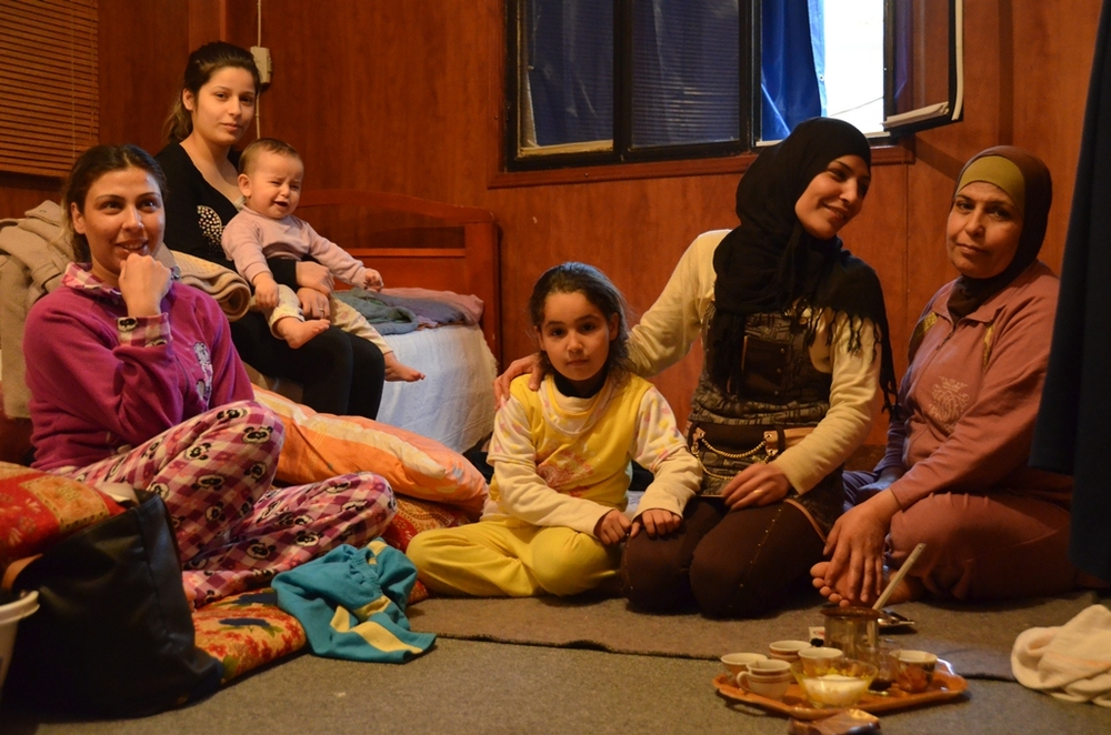 Manal Tayyar and her family sit in a small rented room in Tyre, in South Lebanon, after fleeing their homes in Rural Damascus, Syria