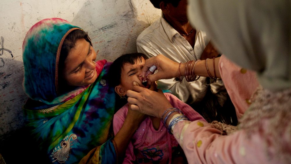 A toddler receives polio drops from a mobile health clinic, at a school-turned relief camp in Tando Adam, Sanghar district, Sindh province, Pakistan