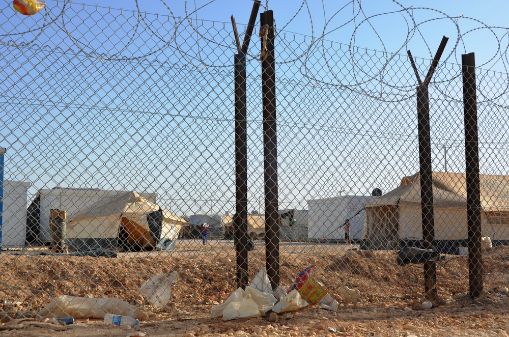 "A barbed wire fence separates the Syrian refugees in Jordan's Za'atari camp from the ""base camp"" where aid organizations have set up their offices. Aid workers have often come under attack during riots in the camp"