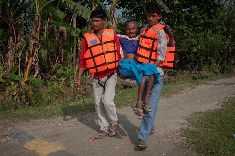 A man with a physical disability is carried by a community member to a flood platform in a village in western Nepal during a community DRR drill