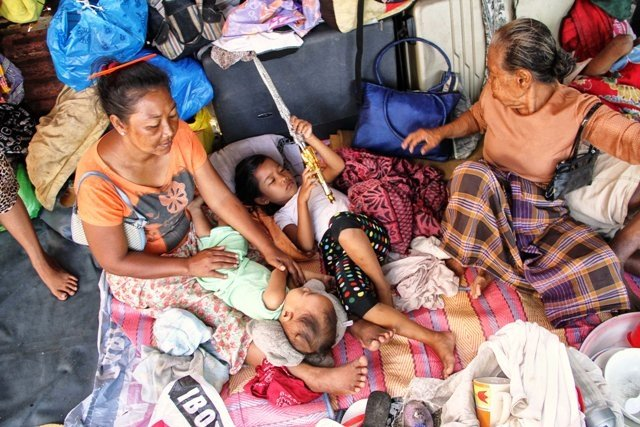 Children are watched over by their grandmothers in a small corner of an evacuation centre in Barangay Baliwasan, Zamboanga City. More than 100,000 people have been displaced after fighting broke out and members of the Moro National Liberation Front (MNLF)