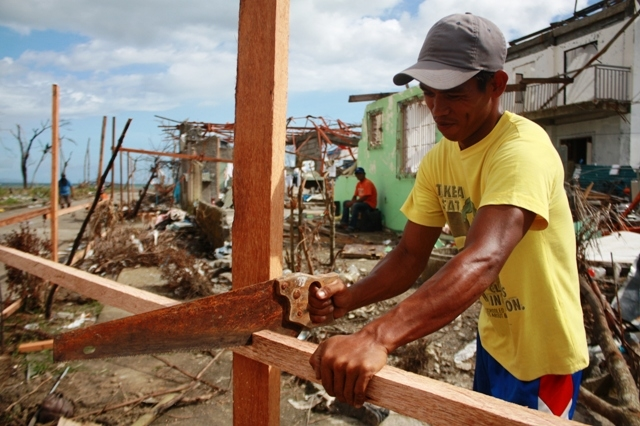 A resident of the typhoon-affected town of Palo works to repair his home one month after Typhoon Haiyan, which struck the central Philippines on 8 November 2013