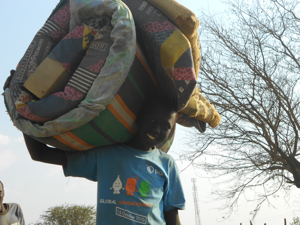 A South Sudanese refugee boy with his belongings after crossing into Uganda at the Elegu border  point. The boy fled fighting in his home village in Bor, Jonglei State's capital. At least 355,000 people have been displaced and thousands killed in South