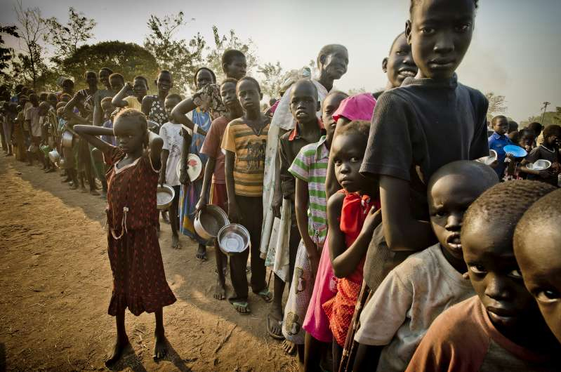 South Sudanese refugees waiting in line to get food at the Dzaipi transit centre in Uganda
