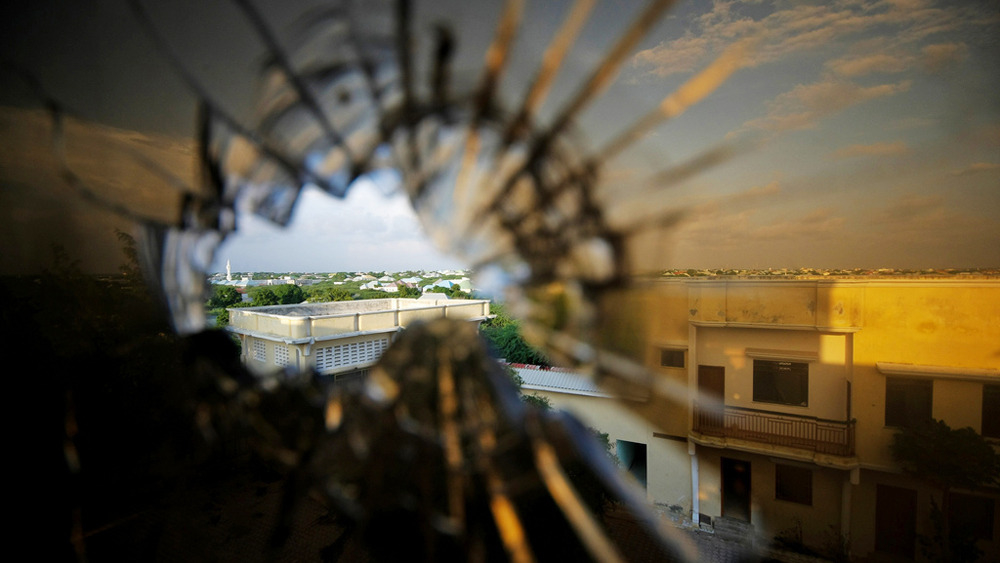 The skyline beyond the northern suburbs of Mogadishu is seen through a bullet hole in the window of a hotel in Yaaqshiid District, where African Union Mission in Somalia (AMISOM) forces have pushed Al Shabaab militants beyond the city's northern fringes t