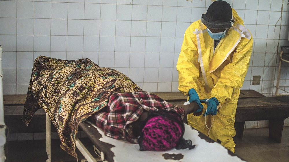 A government health worker in the MOH-led Kenema Ebola Treatment Centre in Sierra Leone attends to a victim. July 2014.