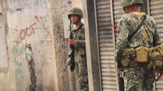 Marines soldiers patrol a community in Zamboanga City. One year after a deadly Muslim rebel siege on the city, the area remains insecure.