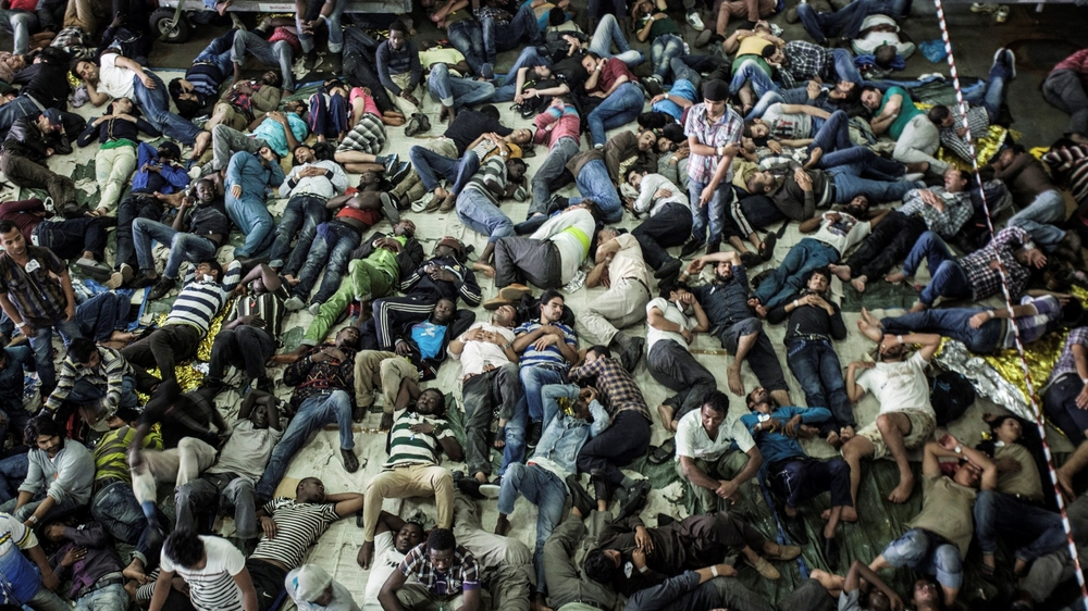 Rescued migrants sleep after being plucked from a boat off the coast of Italy in summer 2014. Thousands of refugees attempt to make the perilous journey to Europe every year, with hundreds dying. In the summer of 2014 the Mare Nostrum search and rescue te