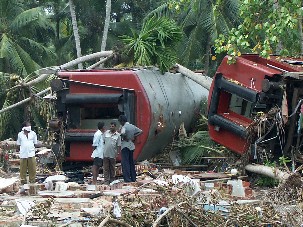 People stand next to two carriages of a train swept away by the tsunami at Peraliya about 90 km south of the capital Colombo, on 28 December 2004. Over 1500 died on the train. (File photo)