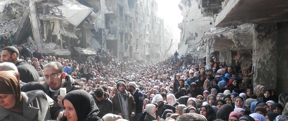 A 2014 photo from the Yarmouk Palestinian camp on the outskirts of Damascus. It shows thousands of Palestinians awaiting aid distribution in the camp.