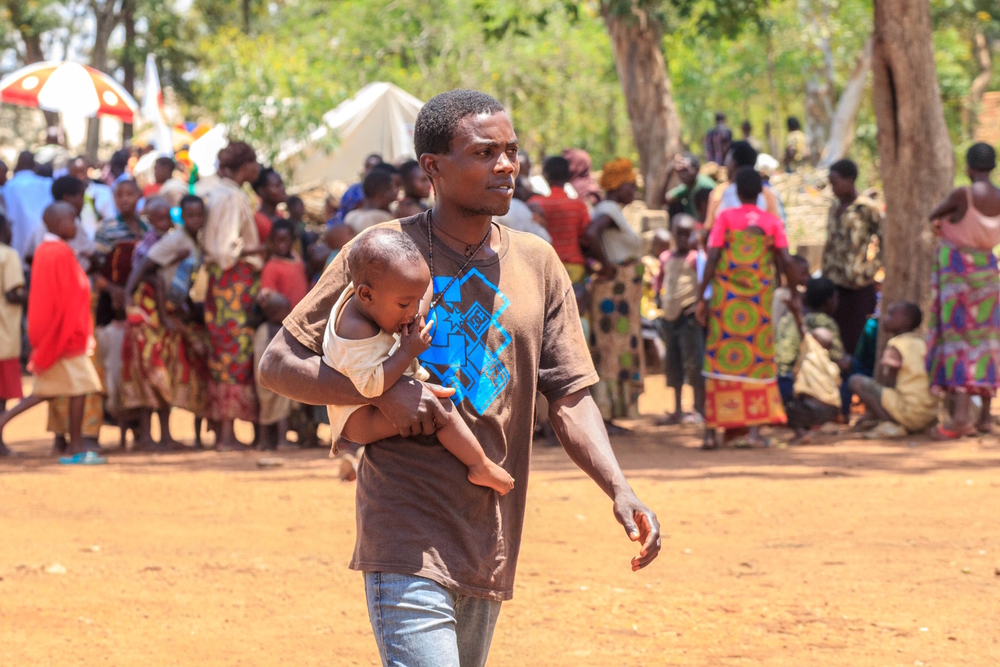 A young man carrying a child next to a registration centre for Burundian refugees in Bugesera, Rwanda in April 2015