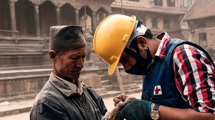 A Red Cross worker tends to an injured Nepali man after an earthquake on Saturday