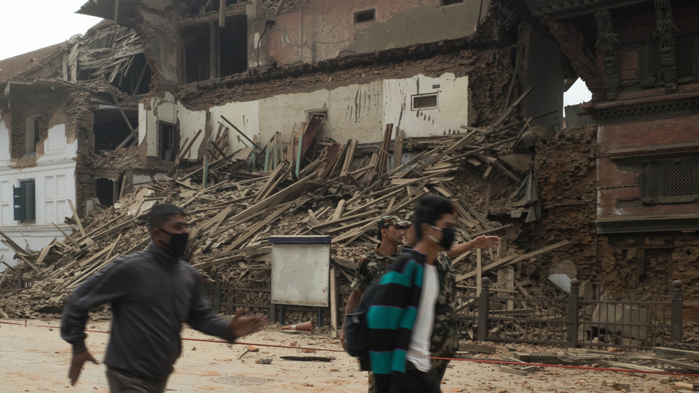 Men run past a collapsed building in Basantapur in central Kathmandu during an aftershock on 25 April 2015. Nepal was struck by a 7.8 earthquake that destroyed historic buildings and crucial infrastructure.