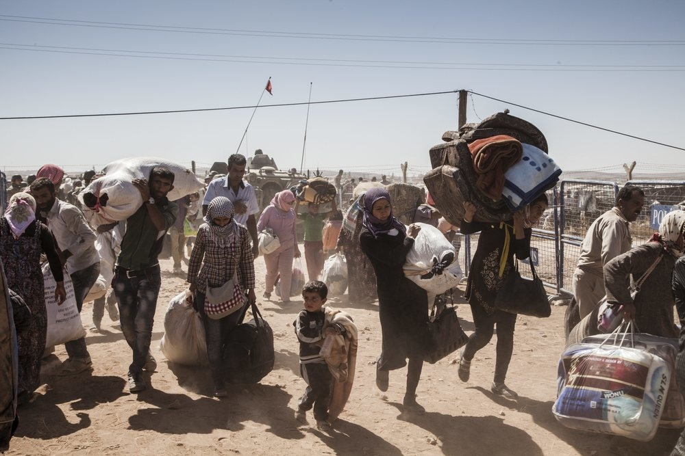 Syrian Kurdish refugees cross into Turkey from Syria, near the town of Kobani. Syria's conflict, which began in 2011, has turned the country into the world's single largest driver of displacement.