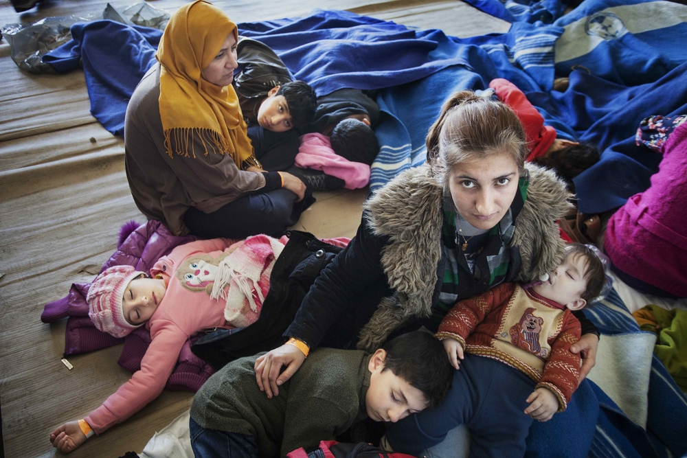 A Syrian refugee mother comforts her children, after being rescued from a fishing boat carrying 219 people who had hoped to reach Europe.
