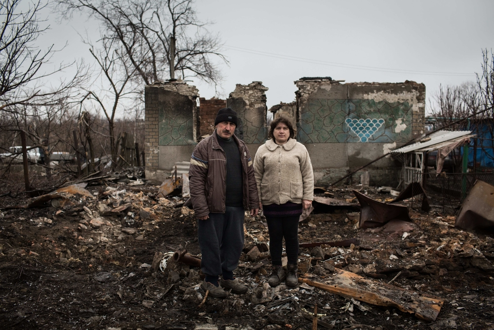 Yurvi and Tatiana stand in the ruins of their home in Nikishino, eastern Ukraine. The couple's home was hit during fighting in the village and was completely destroyed.
