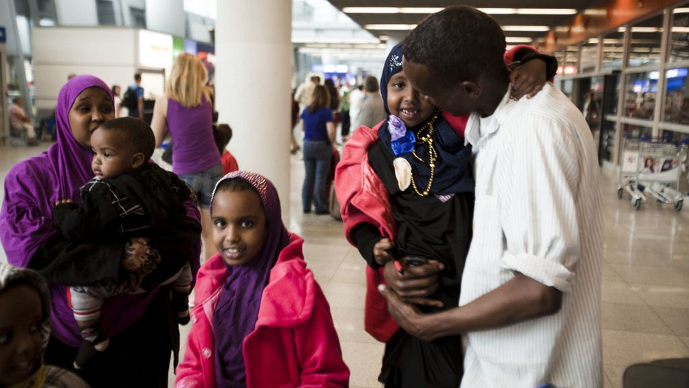 Mohad, a Somali refugee, reunites with his wife and children at Warsaw airport in Poland after five years apart