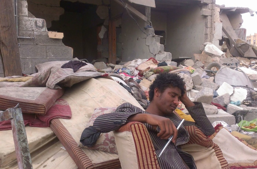 A Yemeni man sits outside the ruins of his home which was destroyed in an airstrike by the Saudi Arabian-led coalition