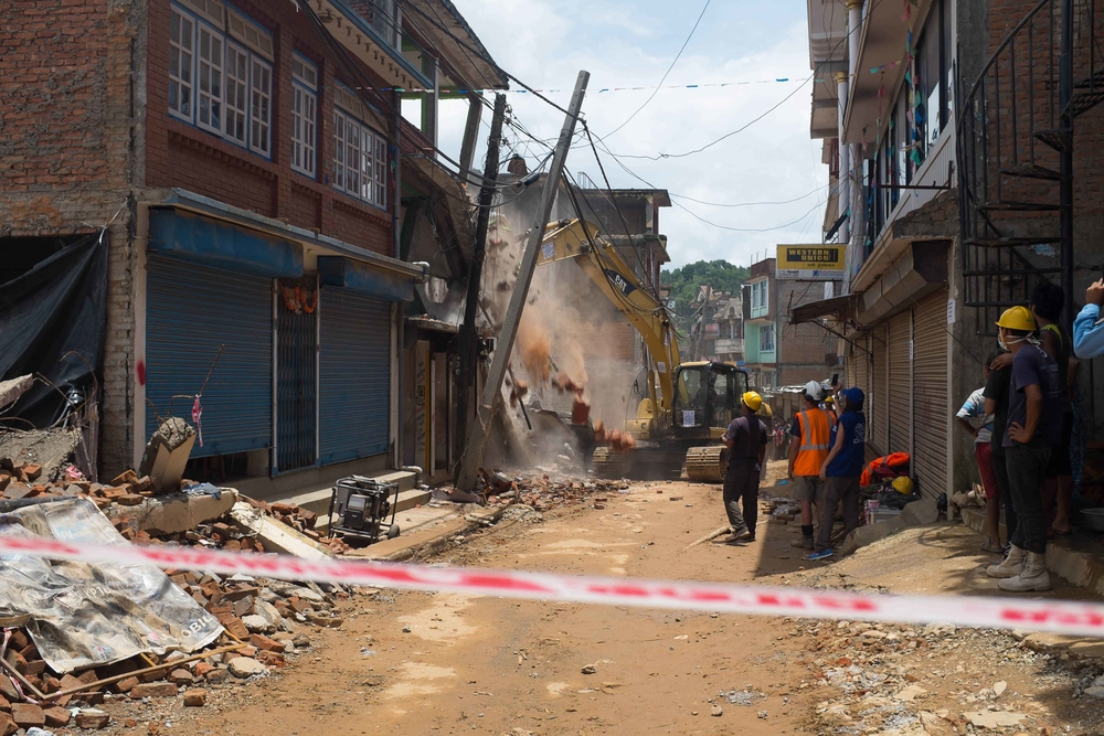 Workers and residents watch as a bulldozer demolishes an earthquake-damaged building in the city center in Chautara, Nepal, on 8 July 2015
