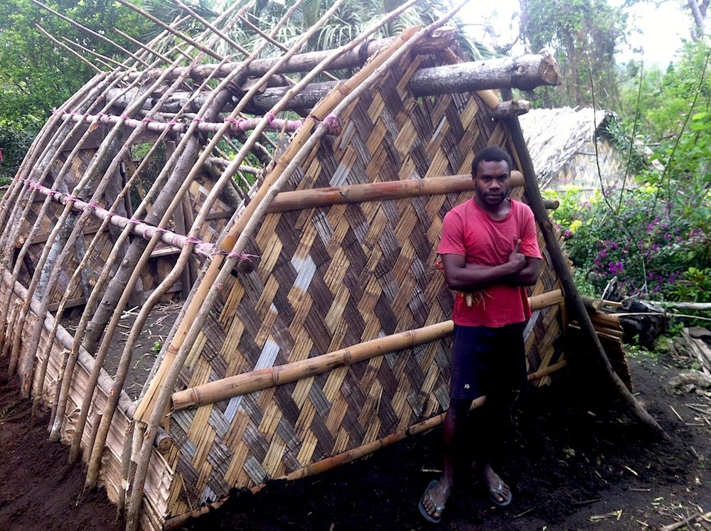 Charlie Kalah stands by a traditional dwelling he is building in his village of Yakel on Tanna Island, Vanuatu, which was devastated by Cyclone Pam in March 2015