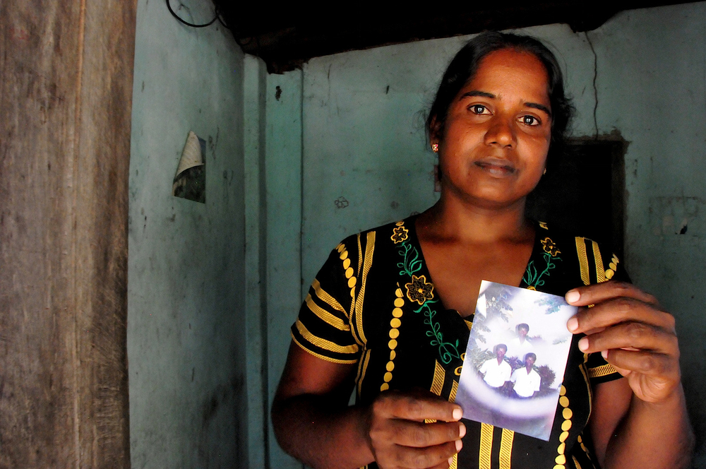 Vijitha Pavanendran holds a photo of her husband who was killed by unknown attackers during Sri Lanka's civil war
