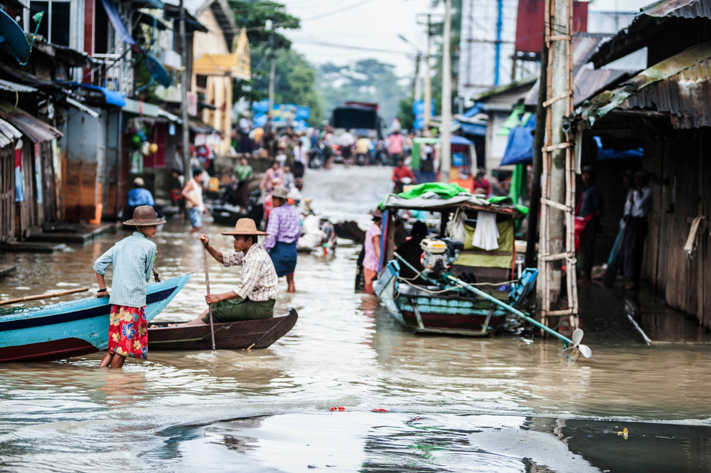 People wade through flooded streets on the outskirts of Pathein in Myanmar in September 2015, where flooding has persisted for months.